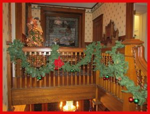 holiday decorated upstairs staircase with stained glass window in background