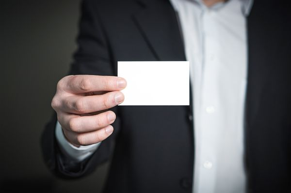 photo of man holding a blank business card
